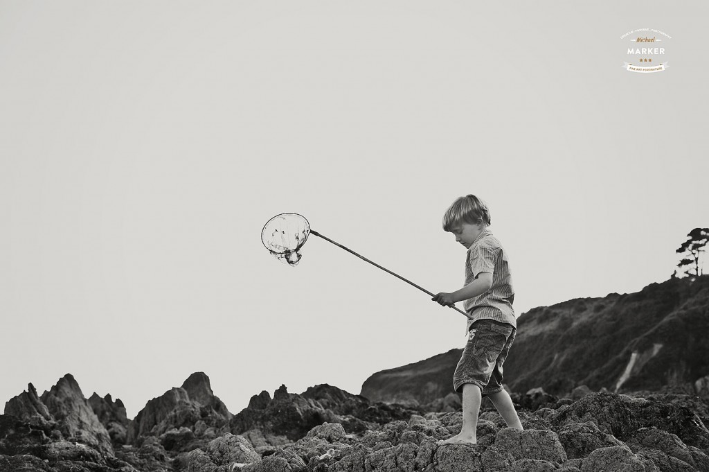 Portrait of Young boy with fishing net walking across rocks on Devon beach